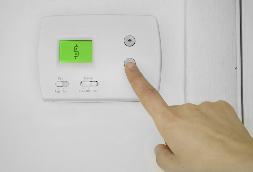 Person lowering bills on thermostat